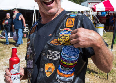 man showing off patches at Bikefest